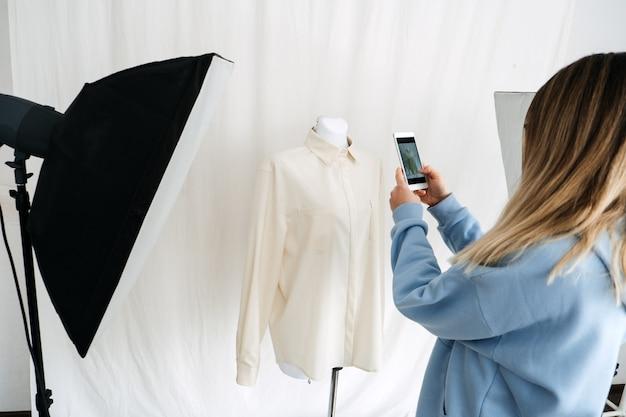 Tecnologia ar vr nel settore della moda. stilista femminile che spara abiti su manichino tramite telefono cellulare per applicazioni di realtà aumentata. soluzioni ar vr nella moda e nel commercio al dettaglio.