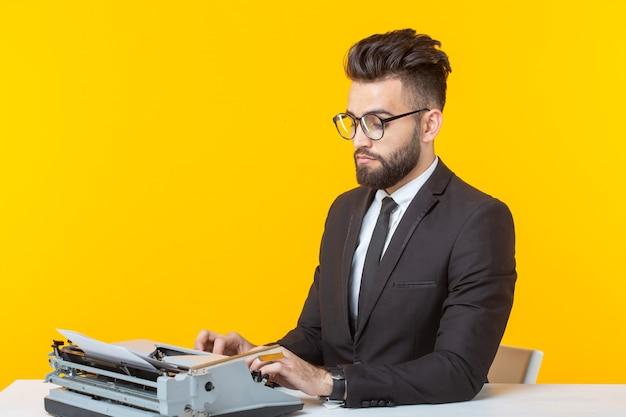 Uomo d'affari arabo o manager in abito formale digitando il testo su una macchina da scrivere su uno sfondo giallo