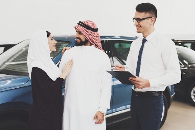 L'uomo di famiglia e wman arabi discutono l'acquisto di automobile.