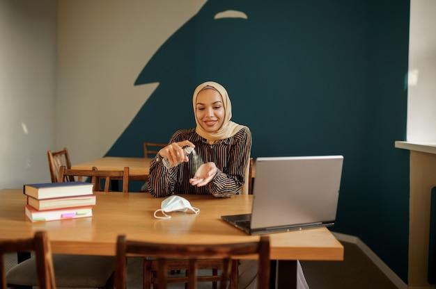 Studentessa araba in hijab disinfetta le mani prima di utilizzare il computer portatile nella caffetteria universitaria. donna musulmana con libri seduti in biblioteca.