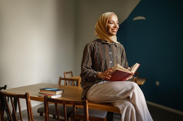 La studentessa araba in hijab tiene il libro di testo nel caffè dell'università. donna musulmana con libri seduti in biblioteca