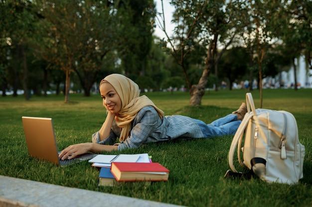 Studentessa araba in hijab sdraiato sull'erba con il computer portatile nel parco estivo. donna musulmana con libri che riposa sul prato