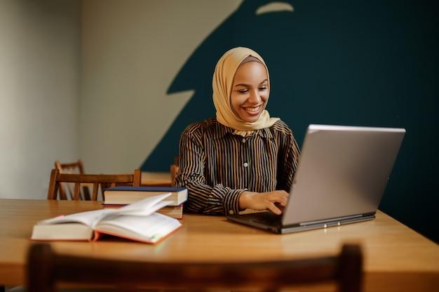 Studentessa araba in hijab utilizzando il computer portatile nel caffè universitario. donna musulmana con libri seduti in biblioteca.