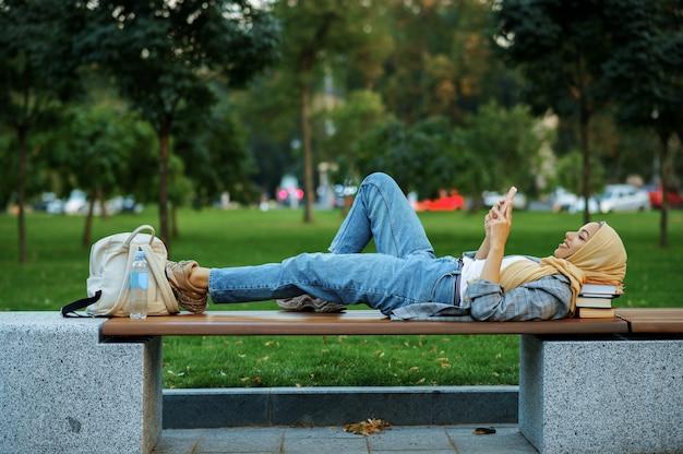 Studentessa araba sdraiata sulla panchina nel parco estivo. donna musulmana che riposa sul sentiero a piedi.