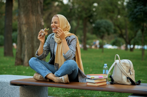 Studentessa araba seduta sulla panchina nel parco estivo. donna musulmana che riposa sul sentiero a piedi.