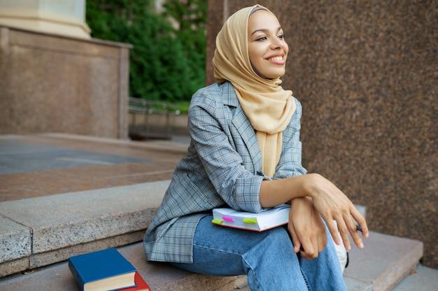 Studentessa araba che si siede sulle scale all'università. una donna musulmana applica il trucco all'ingresso del centro commerciale.
