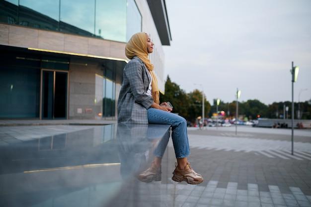 Ragazza araba in hijab posa presso l'edificio nel centro cittadino. donna musulmana all'ingresso del centro commerciale.