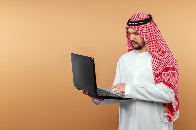 Un uomo arabo, un uomo d'affari, uno sceicco lavora al portatile. investimenti, affari, lavoro via internet, contratti online.