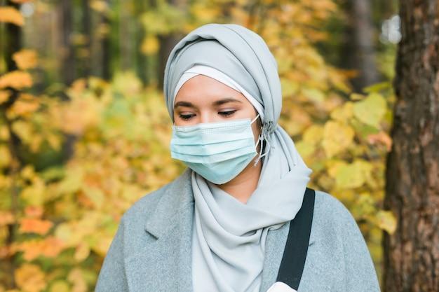 Donna musulmana araba che indossa una maschera facciale per proteggersi dal coronavirus all'aperto
