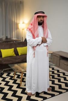 Arabi in turbante che pregano al fatihah con due braccia incrociate vicino al tavolo