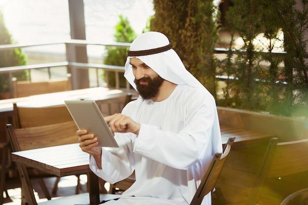 Uomo d'affari arabo saudita che lavora online con un laptop e un tablet in una caffetteria o in un bar con una terrazza all'aperto sullo sfondo. concetto di business, finanza, tecnologie moderne, start up.