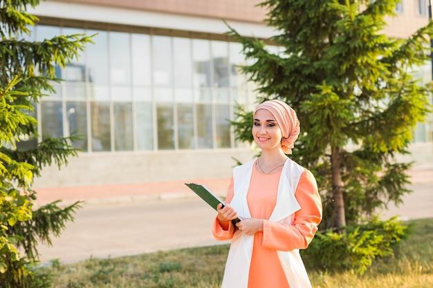 Studente arabo che tiene una cartella. giovane bella donna musulmana a piedi in città.