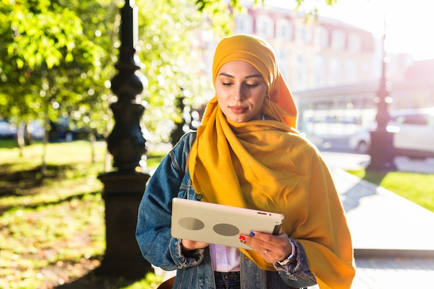 Studentessa araba. bella studentessa musulmana che indossa il tablet hijab giallo brillante.