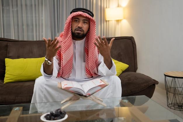 Un giovane arabo che legge il corano con l'espressione delle mani che guarda in alto