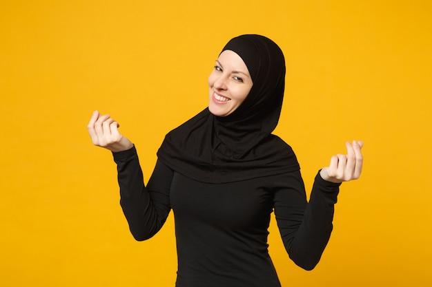 Donna musulmana divertente araba in abiti neri hijab strofinando le dita mostrando gesto in contanti chiedendo soldi isolati sulla parete gialla. concetto di stile di vita dell'islam religioso della gente.