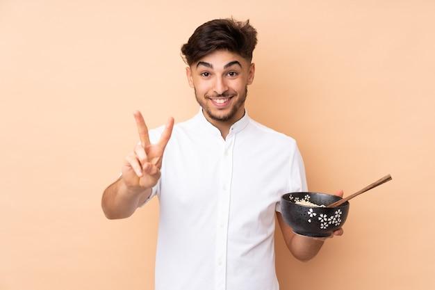 Uomo bello arabo isolato su beige sorridente e mostrando il segno di vittoria mentre si tiene una ciotola di spaghetti con le bacchette