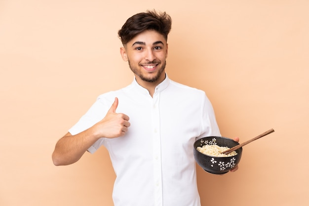 Arabian bell'uomo isolato su beige con i pollici in su perché è successo qualcosa di buono mentre si tiene una ciotola di spaghetti con le bacchette