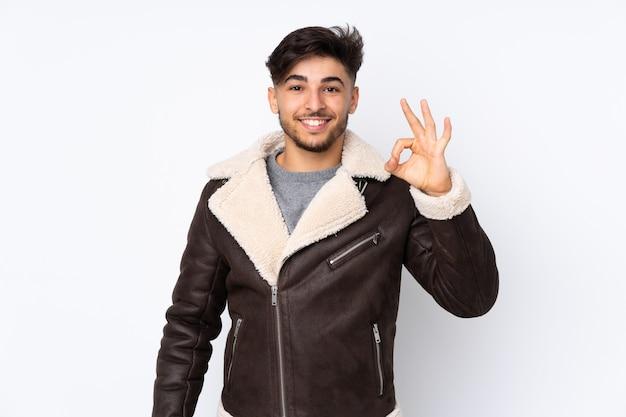 Uomo bello arabo sopra la parete isolata che mostra segno giusto con le dita