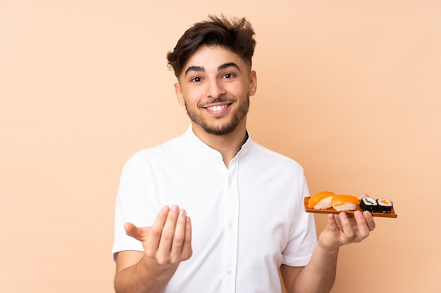 Uomo arabo che mangia sushi isolato su beige che invita a venire con la mano. felice che tu sia venuto