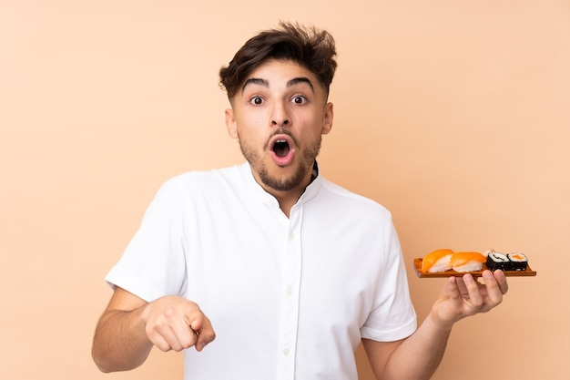 Uomo arabo che mangia sushi isolato sulla parete beige sorpreso e che indica la parte anteriore