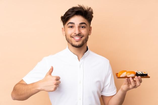 Uomo arabo che mangia sushi isolato sul muro beige con i pollici in su perché è successo qualcosa di buono