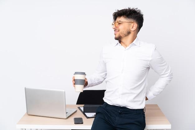 Uomo arabo in un ufficio isolato sul muro bianco che soffre di mal di schiena per aver fatto uno sforzo