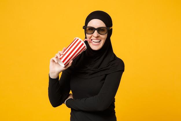 Donna musulmana araba in abiti neri hijab 3d occhiali imax guarda film film tenere carta tazza di soda isolato sul ritratto muro giallo concetto di stile di vita della gente. .