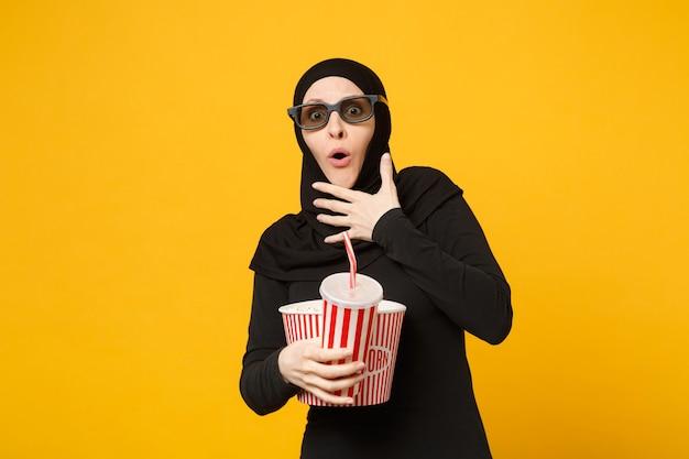 Donna musulmana araba in abiti neri hijab 3d occhiali imax guarda film film tenere popcorn, tazza di soda isolata sul ritratto muro giallo. concetto di stile di vita della gente. .