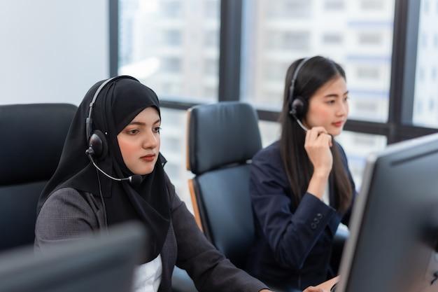 Una donna araba o musulmana lavora in un operatore di call center e un agente del servizio clienti che indossa cuffie con microfono