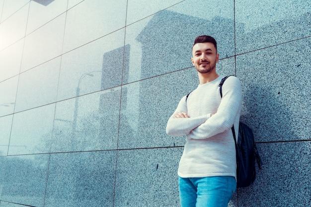 Studente arabo con zaino in piedi vicino al muro esterno