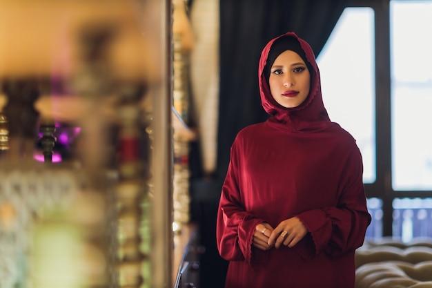 Giovane donna musulmana araba seduta in un caffè a