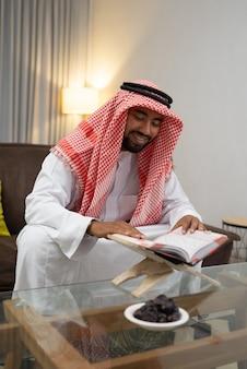 Un giovane arabo è felice mentre legge il corano