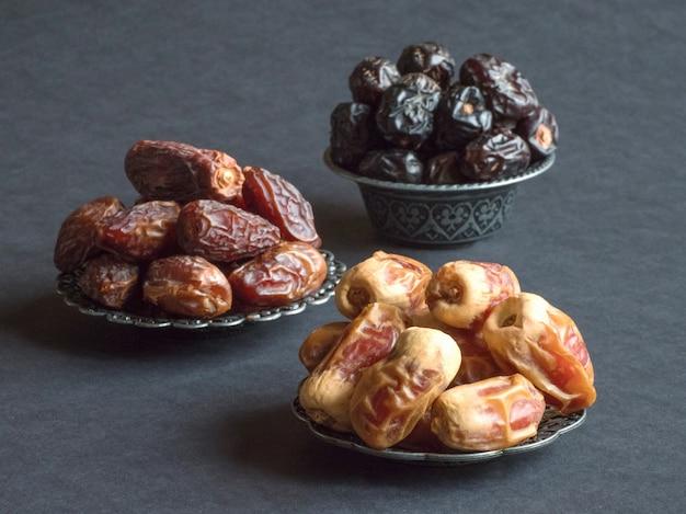 Le date arabe dei frutti sono disposte su un tavolo scuro.