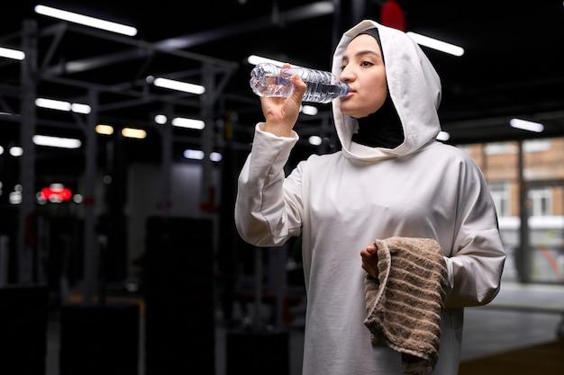La femmina araba ha riposo e relax dopo un duro allenamento bevendo acqua fresca, godersi il tempo libero, amare la salute. concetto di sport