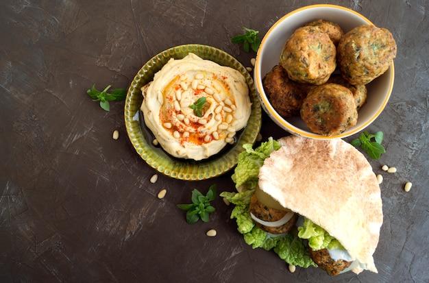 Cibo arabo hummus e falafel su uno sfondo grigio.