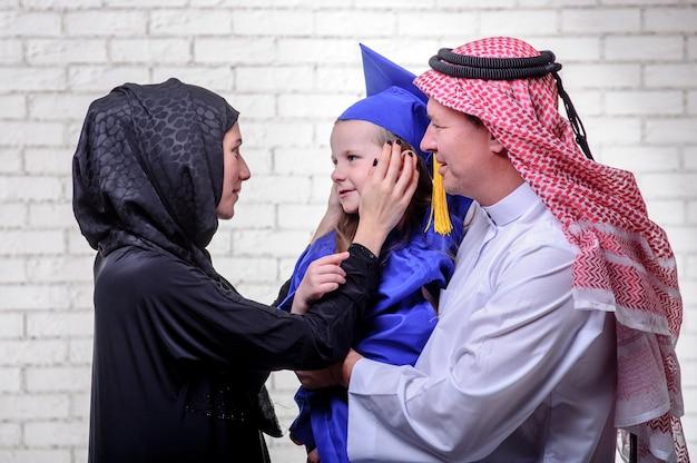 Famiglia del medio-oriente araba che posa con la figlia laureata su fondo bianco
