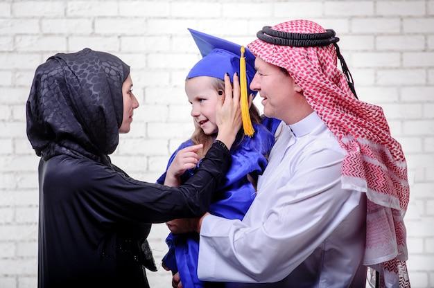 Famiglia del medio-oriente araba che posa con la figlia laureata su fondo bianco Foto Premium