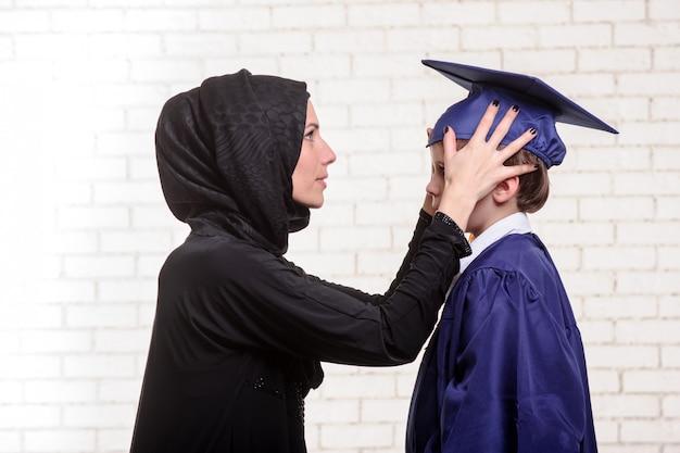 Madre araba che posa con il figlio laureato Foto Premium