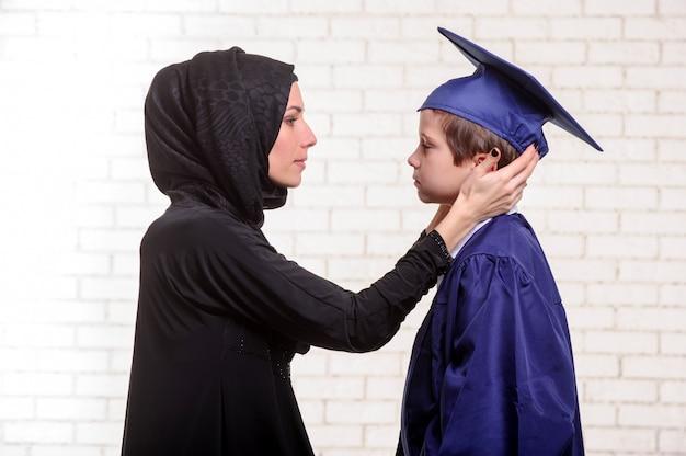 Madre araba che posa con il figlio laureato