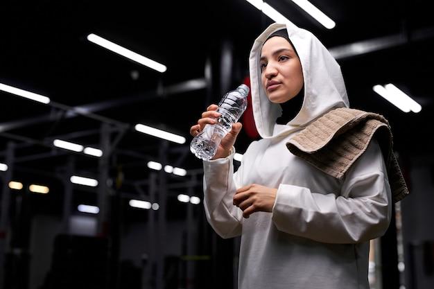 Donna araba in hijab andando a prendere un sorso d'acqua durante l'allenamento in palestra, fare una pausa, riposarsi, indossando l'hijab sportivo bianco