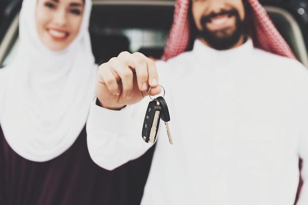 L'uomo arabo compra l'auto tiene il concetto del contratto di chiavi.