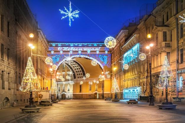L'arco di trionfo in piazza del palazzo a san pietroburgo e le decorazioni di capodanno alla luce di una notte invernale blu. didascalia: felice anno nuovo!