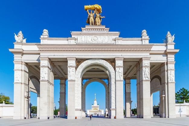 Arco sopra l'ingresso principale al parco vdnh a mosca contro il cielo blu al mattino di sole estivo