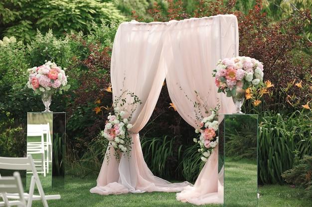 Arco e sedie per la cerimonia nuziale, addobbati con stoffe e composizioni floreali