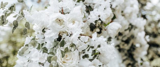 Decorazioni ad arco con fiori bianchi per una cerimonia di matrimonio nella natura
