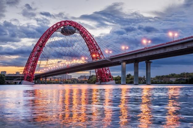 L'arco del pittoresco ponte di mosca in una serata nuvolosa estiva e il riflesso delle lanterne