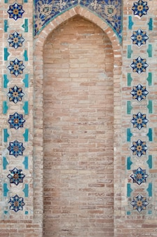 Arco e muro di mattoni con mosaico. i dettagli dell'architettura medievale dell'asia centrale