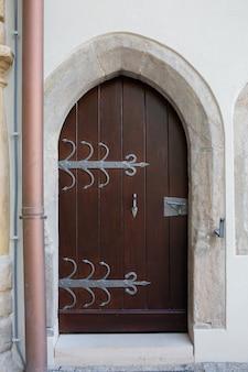 Porta ad arco in legno con maniglia e forgiatura fatti a mano. colpo all'aperto