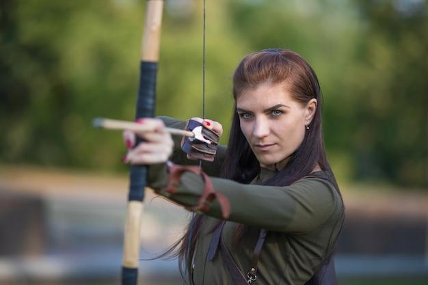 Donna di tiro con l'arco con tiro con l'arco sulla foresta