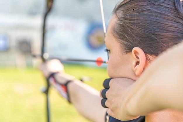 Tiro con l'arco, giovane donna con una freccia in un arco focalizzata sul colpire un bersaglio